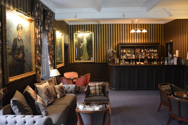 Relax with a whisky by the fire in the bar at Bunchrew House